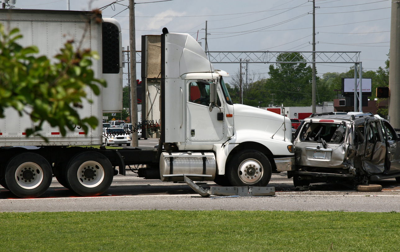 scene after a large tractor trailer semi truck crashed into a smaller vehicle