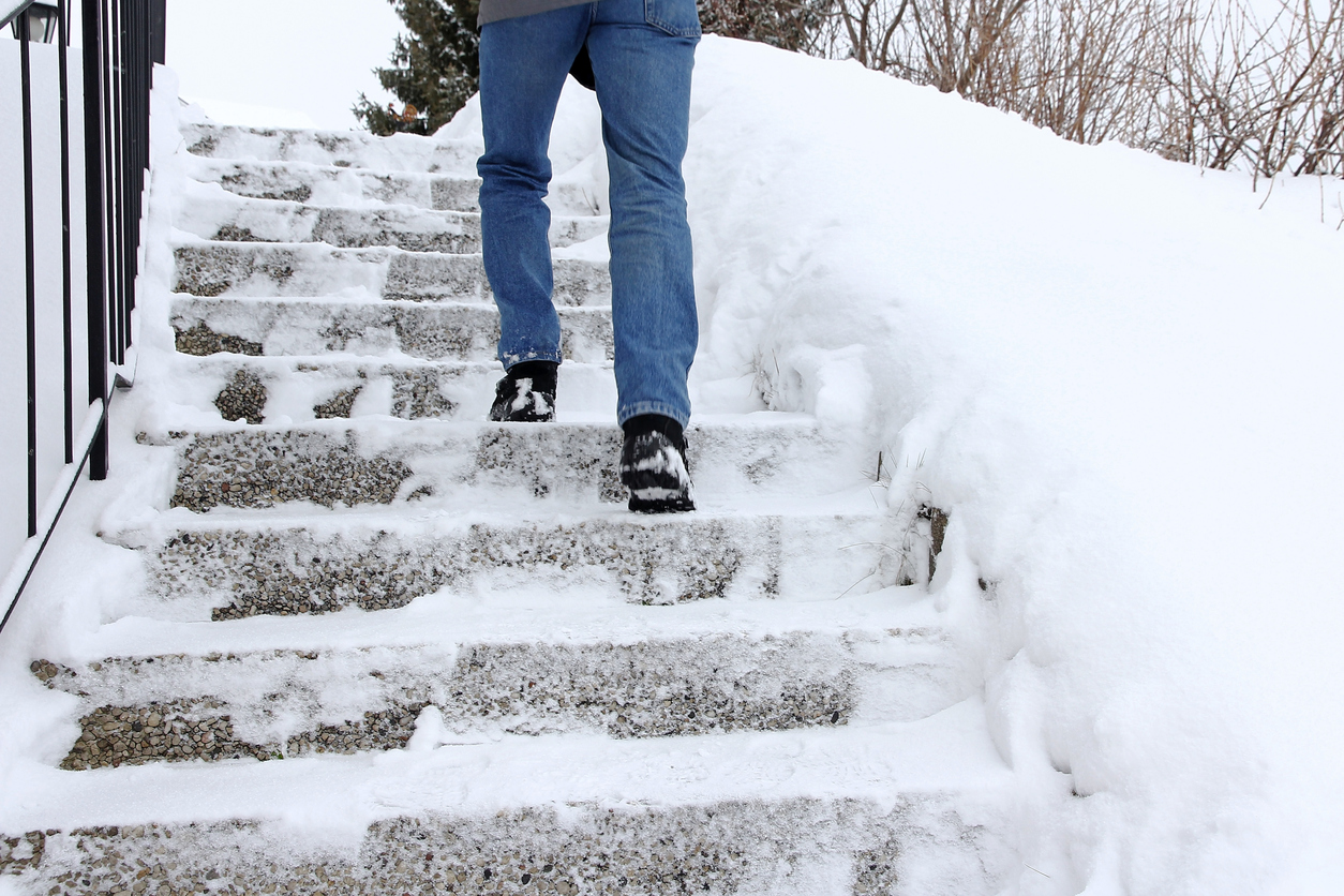 person walking up a snow covered staircase in danger of slipping and falling