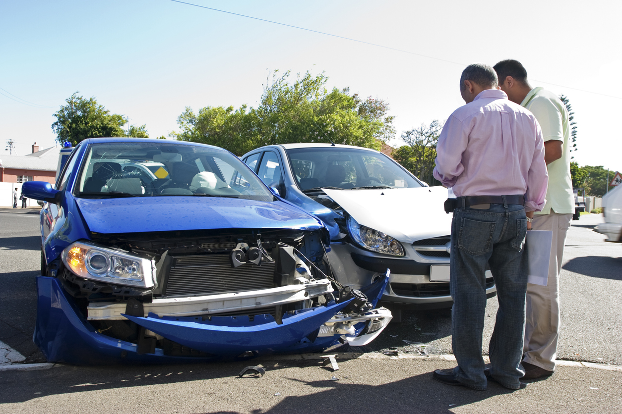 Two men next to two damaged cars after an accident