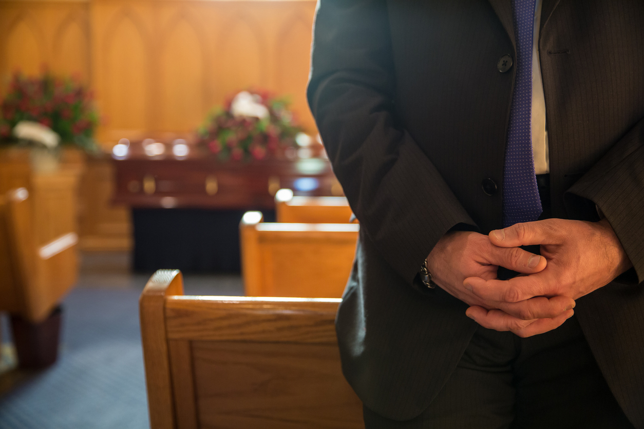 person with hands clasped inside a chapel before a funeral service